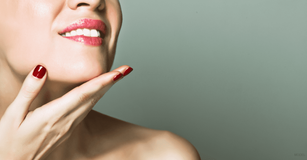 Close-up of a woman's hand touching her smooth neck following several nonsurgical skin and neck treatments.