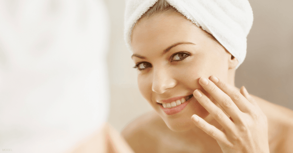A woman looks in the mirror after a shower to observe her smooth, radiant skin following a chemical peel.
