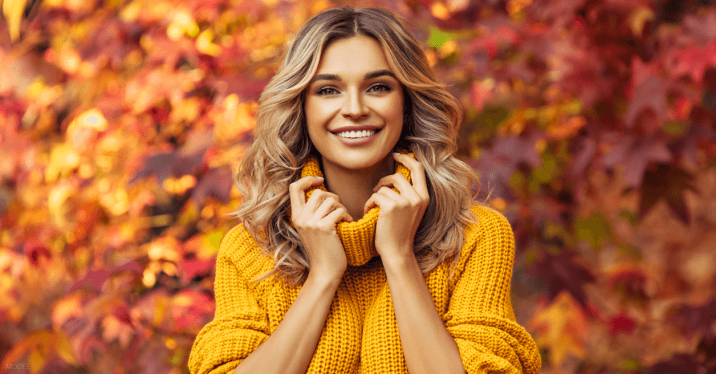 A woman in a yellow sweater stand among fall foliage.