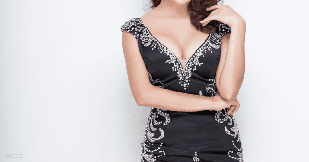 Mid-shot of a woman who has had breast augmentation wearing a black dress.