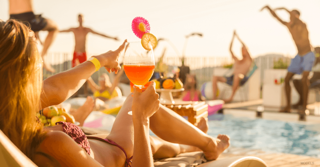 People relax by the pool on a warn day.